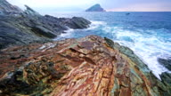 Calm waves splash on rocky shore video