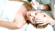Calm woman enjoying skin care treatment at wellness center video