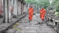 Cambodian monks walking at Bayon exterior video