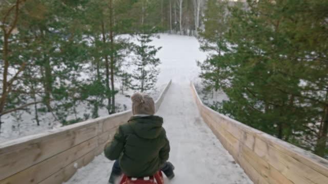 Camera Following Boy Sledding in Winter video