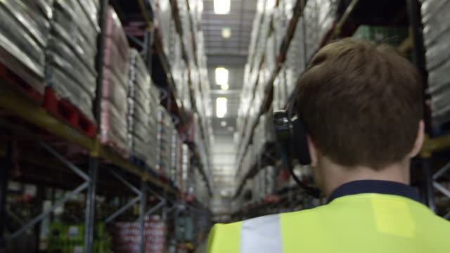 Camera follows man locating stock in warehouse, shot on R3D video