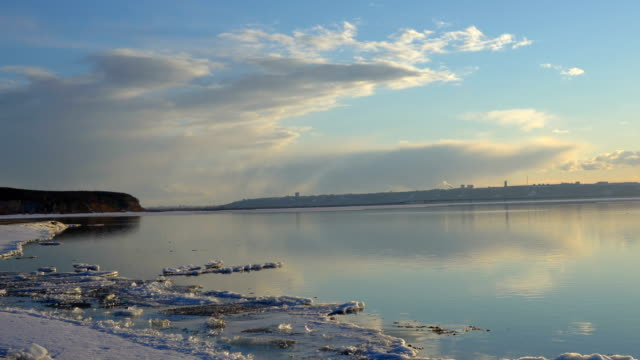 Camera inspects the surface of a pond (lake). The water surface is partially opened from the ice. There is no wind and therefore the lake is calm. Clouds and sky reflected in the surface of the water. Away on the other side see the city.  Red sun is at su video