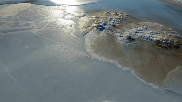 Camera moves over the ice surface. Surface is covered with snow and ice. The sun's rays shine on the ice. Frosty winter day. video