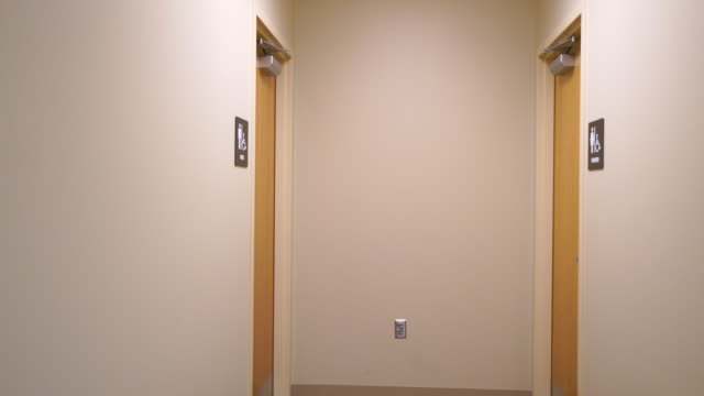 Camera moving down hallway towards Men's Bathroom Sign video