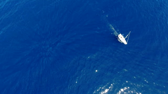 Camera rotation aerial shot with sailboat against navy blue water suface video
