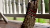 Camera slides past old destroyed broom leaning on porch fence video