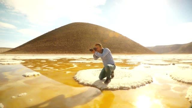 Cameraman kneeling does photo on salt islet on background volcano Meke lake Karapinar video