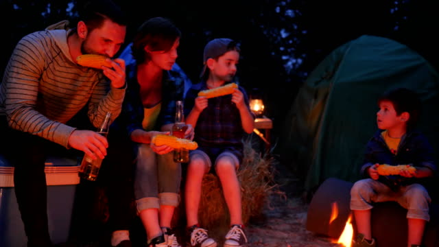camp, young parents with children eat corn and drinking beer in holiday in campground, happy family eating video