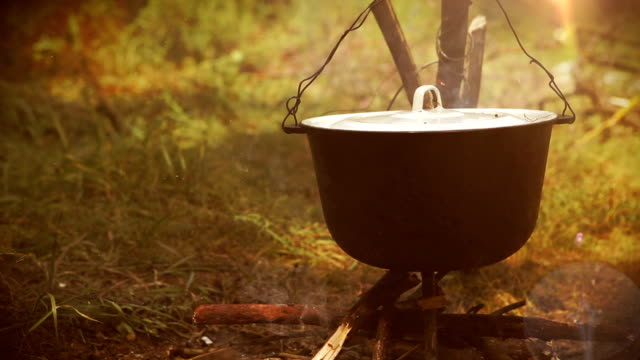 Campfire scene: a pot with food hangs over the fire video