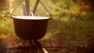 Camping scene: a pot with food being prepared hangs over the bonfire video