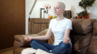 Cancer patient woman sits on a sofa and meditates video