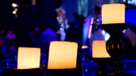 Candelstick with 4 lighting candels, people celebrating  in the party video