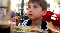 Candid casual shot of young boy eating meal. Child laughing and smiling while eating lunch video