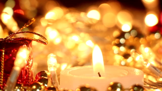 candle and christmas lights close-up out of focus video