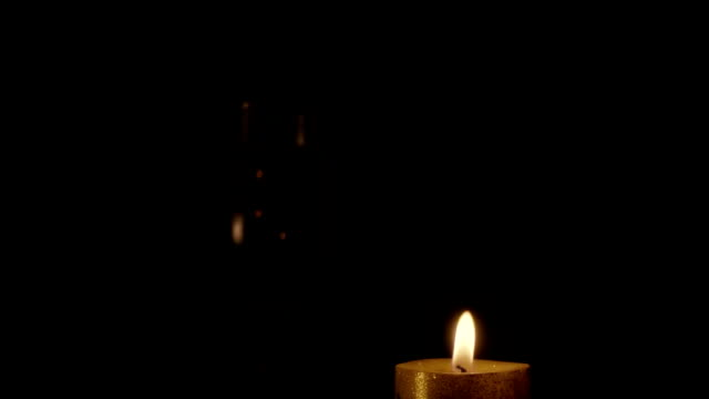 Candle burns on a black background. Slow motion video