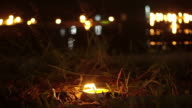 Candle lit at night to pay respect to river goddess at Loi Krathong festival Thailand. video