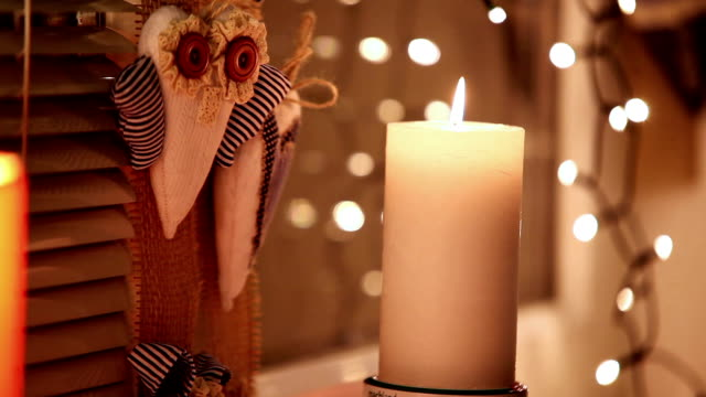 Candle on the windowsill with christmas lights background video