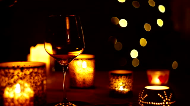 Candlelit New Year's Eve dinner: wine pouring into a glass with Christmas tree background video