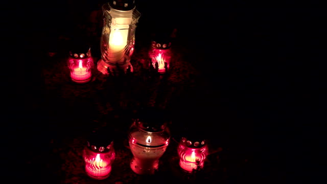 Candles burning on graves at cemetery at night. All Hallows Eve. FullHD video