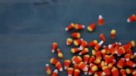 candy corn for halloween slides across a wood background in slow motion video