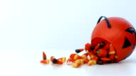 candy corn spills out of a pumpkin container in slow motion video