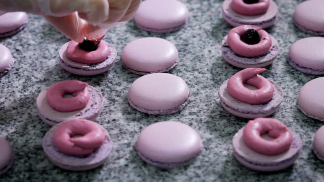 Candy store. Decoration of the French macaroons. The worker of a candy store in gloves adds cream and berries to a ready dessert. Thus decorating a dessert video