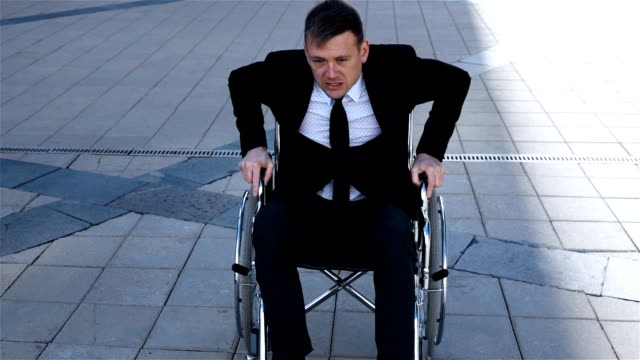 Capable handicapped businessman trying to get up from the wheelchair video