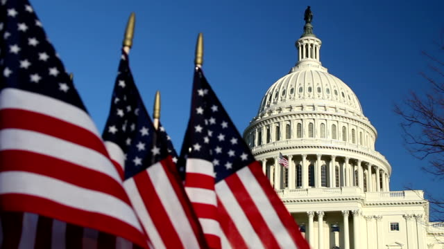 US Capitol dome with American flags in foreground - CU video
