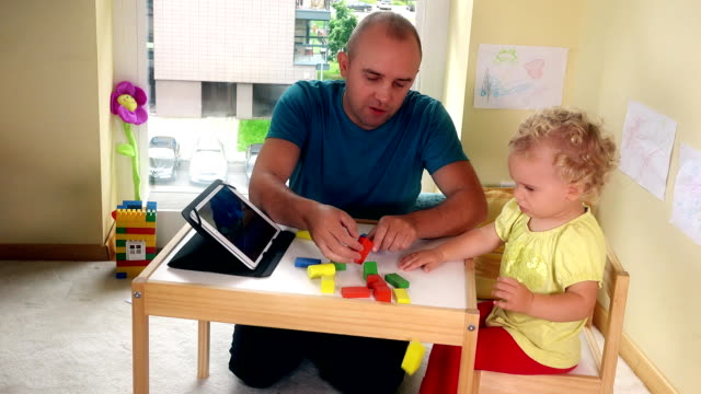 Capricious child dont want play with bricks and father give daughter tablet video