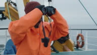 Captain of Commercial Fishing Ship Dressed in Protective Coat Looking through Binoculars video