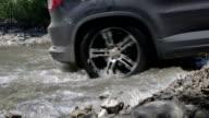 Car crossing mountain creek closeup video