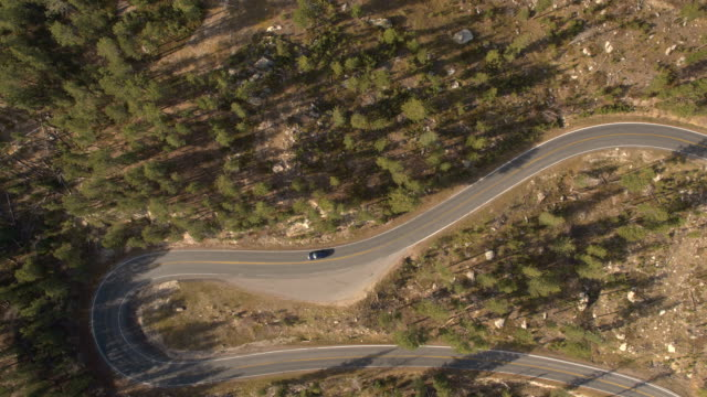 AERIAL: SUV car descending from a mountain driving on winding hairpin turn road video