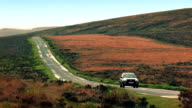 Car Drives Down Hill In Rugged Landscape video