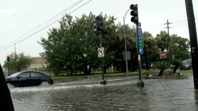 Car drives through a flooded intersection of I10 in New Orleans video