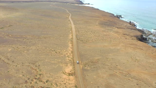 AERIAL: Car driving across huge sandy desert next to ocean video