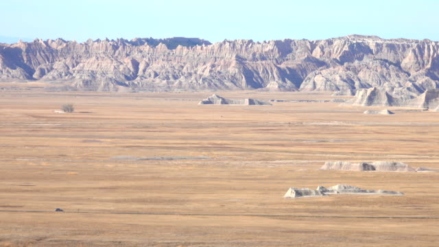 Car driving across the dusty Badlands desert grasslands past the rocky mountains video