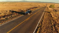 AERIAL: SUV car driving along empty countryside road at sunset video