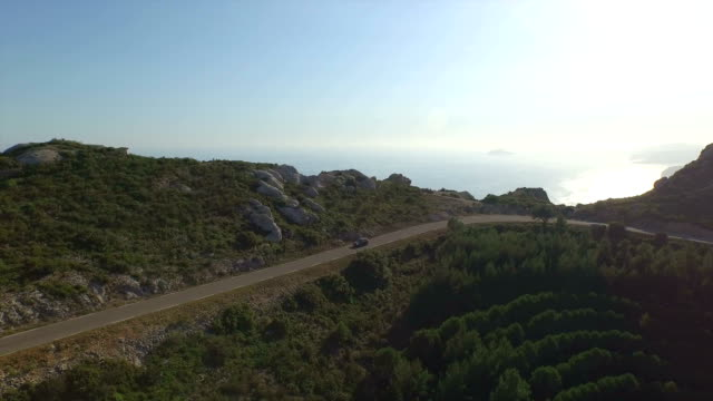 AERIAL: Car driving along mountain pass road in summer evening video