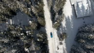AERIAL: Car driving on plowed road among alpine cabins and huts in winter forest video