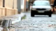 car driving on rainy cobblestones street video