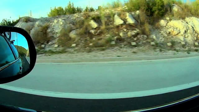 Car driving through the empty road, focus on mirror video
