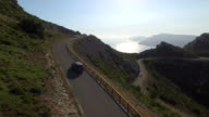 AERIAL: Car driving up the mountain pass above the ocean video