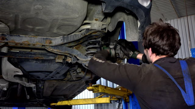 car mechanic with spanner tool strengthen brake system. video