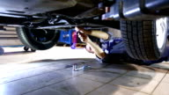 Car mechanic working under a vehicle. video