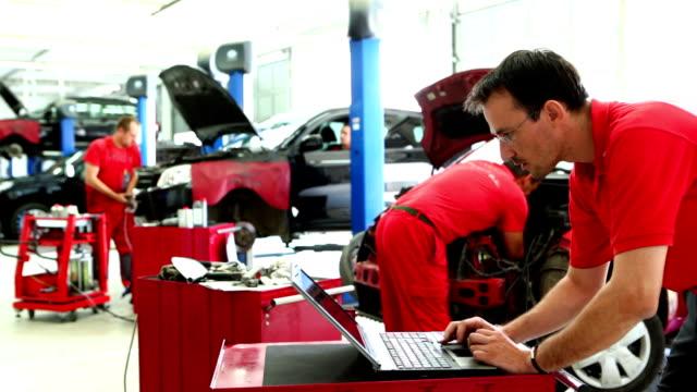 Car mechanics in workshop. video
