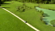 WS AERIAL Car On A Dirt Road Surrounded With Pastures video