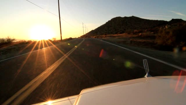 POV of car on road trip. Camera attached on car's hood while driving on deserted highway video