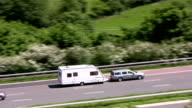 Car towing caravan and white van on motorway video
