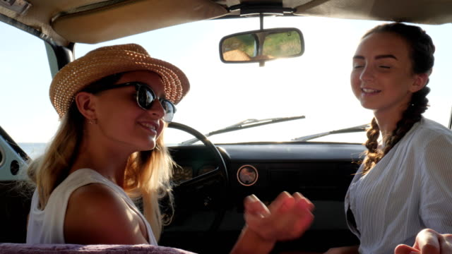 car trips, went with us on car, two girl in automobile in sunlight, females into auto at background nature in slow motion video