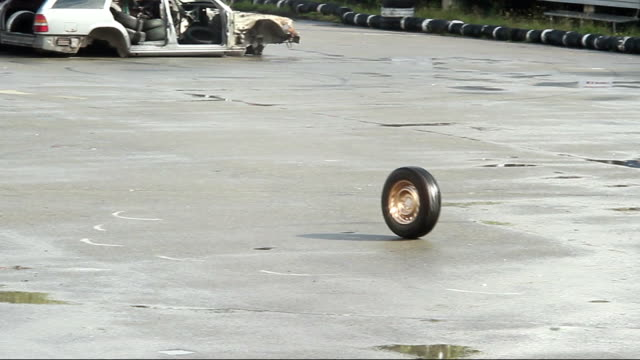 Car wheel rolling on asphalt after accident, crash. Junkyard video